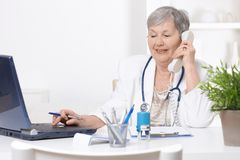 Senior doctor using laptop computer Royalty Free Stock Photos