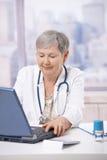 Senior doctor using laptop computer. Senior female doctor, working at desk, using laptop computer. Looking at screen, smiling Royalty Free Stock Photography