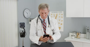 Senior doctor using smartphone in the office stock photo