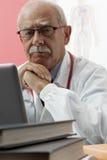 Senior Doctor Using Webcam. Senior doctor speaking with patient through webcam Stock Image