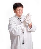 Senior doctor wearing latex gloves Stock Photography