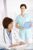 Senior doctor working at desk with assistant Royalty Free Stock Photography