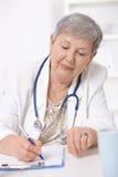 Senior doctor writing notes Stock Photos