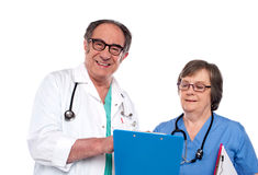 Senior doctors reading medical report. Isolated against white background Stock Images