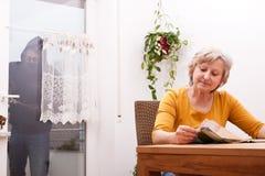 Senior does not note the burglar. Female senior does not note the burglar stock photography