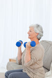 Senior doing her exercises on her sofa Royalty Free Stock Image
