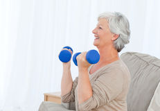 Senior doing her exercises on her sofa Royalty Free Stock Photography