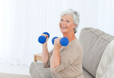 Senior doing her exercises on her sofa Stock Photo
