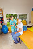 Senior doing remedial gymnastics. In physiotherapy with nurse Stock Photos