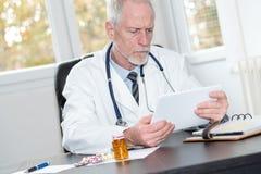 Senior doktorska używa pastylka Fotografia Stock