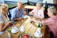 Senior dominoes players. Smiling elderly people having tea party in lovely outdoor cafe and playing dominoes enthusiastically Royalty Free Stock Images