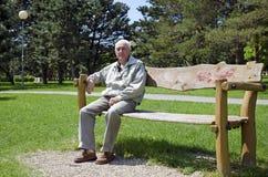 Senior dozing on bench. Senior is dozing on bench in park on housing estate Stock Photo
