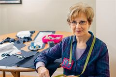 Senior dressmaker posing with sewing materials. Senior dressmaker posing looking at camera with table with sewing materials in the background royalty free stock photos