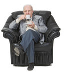 Senior drinking coffee. Senior man drinking coffee while is sitting in an armchair Stock Image