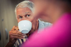 Senior drinking coffee during discussion. In the retirement house Royalty Free Stock Photos