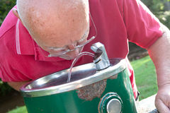 Senior Drinking from Fountain. Senior man drinking water from a fountain outside on a sunny day Royalty Free Stock Photos