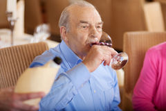 Senior drinking a glass of red wine in restaurant Stock Image