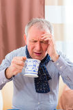 Senior drinking tea to cure flu Royalty Free Stock Images
