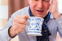 Senior drinking tea to cure flu Stock Image
