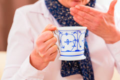 Senior drinking tea to cure flu Royalty Free Stock Image