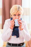 Senior drinking tea to cure her flu. Old woman drinking tea to cure her bad cold or flu at home royalty free stock image