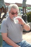 Senior drinking water. Baby boomer man with gray hair and glasses in park drinking water Royalty Free Stock Photography