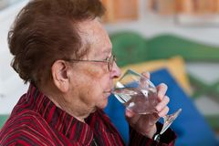 Senior drinking water from a glass. Old woman drinking water from a glass stock images