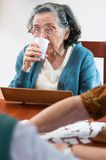 Senior drinking water. And playing rummy Stock Images