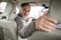Senior drive driving his modern car, going in reverse, royalty free stock photography