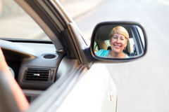 Senior driver. A happy senior female driver looking in her side mirror in car Stock Images