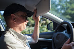 Senior driver hiding from the sun Royalty Free Stock Photo
