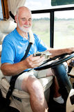 Senior Driver Using GPS. Senior man using GPS navigation to drive his motor home Royalty Free Stock Photography