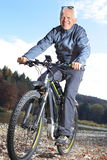 Senior on e-mountain bike beside a river Royalty Free Stock Images