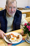 A Senior eating a big breakfast. Royalty Free Stock Photo