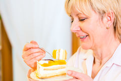 Senior eating cake in the afternoon Stock Photos