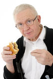 Senior Eating Fast Food. Closeup of a senior man looking at the viewer with a half-eaten hamburger in one hand and a white napkin in the other.  On a white Stock Photography