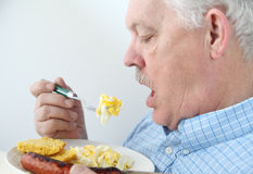 Senior eats breakfast eggs Royalty Free Stock Images