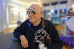 Senior ed il suo cane che collaudano le nuove lenti fotografia stock libera da diritti