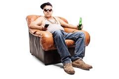 Senior in einer Hip-Hop-Ausstattung, die in einem Lehnsessel sitzt Stockfotos