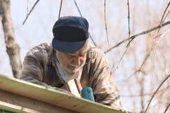 Senior in einer Leiter, die das Dach gestaltet Lizenzfreies Stockfoto