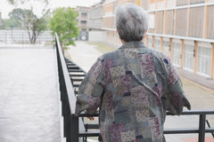 Senior elder standing on balcony looking at the city view, elder Stock Image