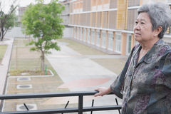 Senior elder standing on balcony looking at the city view, elder. Ly asian mature woman enjoying nice weather on terrace royalty free stock images