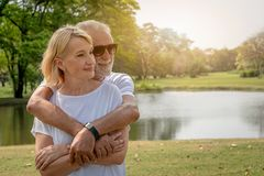 A senior elderly couple cuddle in a park in summer time. With copy space stock images