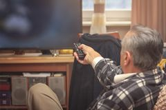 Watching TV at home, enjoying some free time. Senior elderly man changing channels on his modern LCD TV, sitting in his living room Stock Images