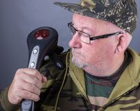 Senior elderly man with an electric infrared massager on his shoulder Royalty Free Stock Photo