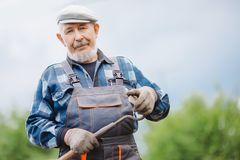 Senior elderly man reclaims soil with hoe on potato field. Concept eco farm vegetable garden royalty free stock photography