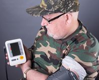 Senior elderly man wearing camouflage clothing checking his blood pressure Royalty Free Stock Photography