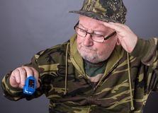 Senior elderly old man wearing camouflage clothing and checking pulse and oxygen levels Stock Photo