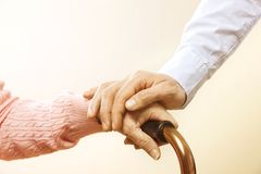 Mature female in elderly care facility gets help from hospital personnel nurse. Close up of aged wrinkled hands of senior woman. G royalty free stock photography
