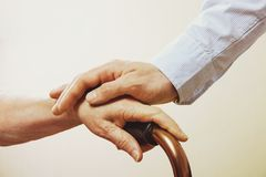Mature female in elderly care facility gets help from hospital personnel nurse. Close up of aged wrinkled hands of senior woman. G royalty free stock image